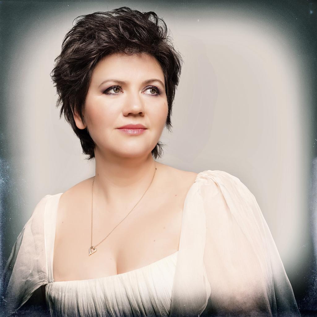Buste de Dana Ciocarlie avec des cheveux mi-long, portant une robe blanche et un petit collier en forme de coeur