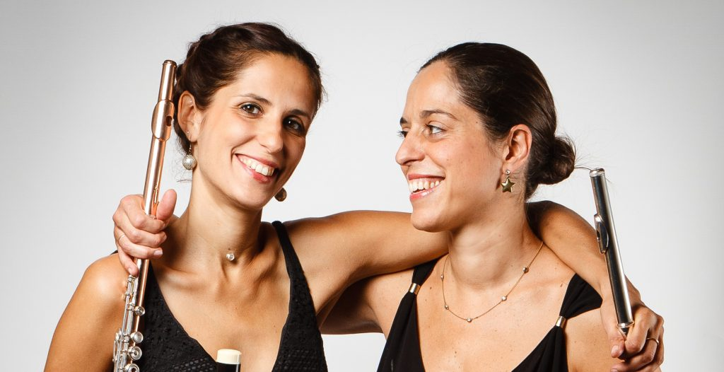 Deux femmes sourient en se tenant par les épaules avec des flûtes à la main.