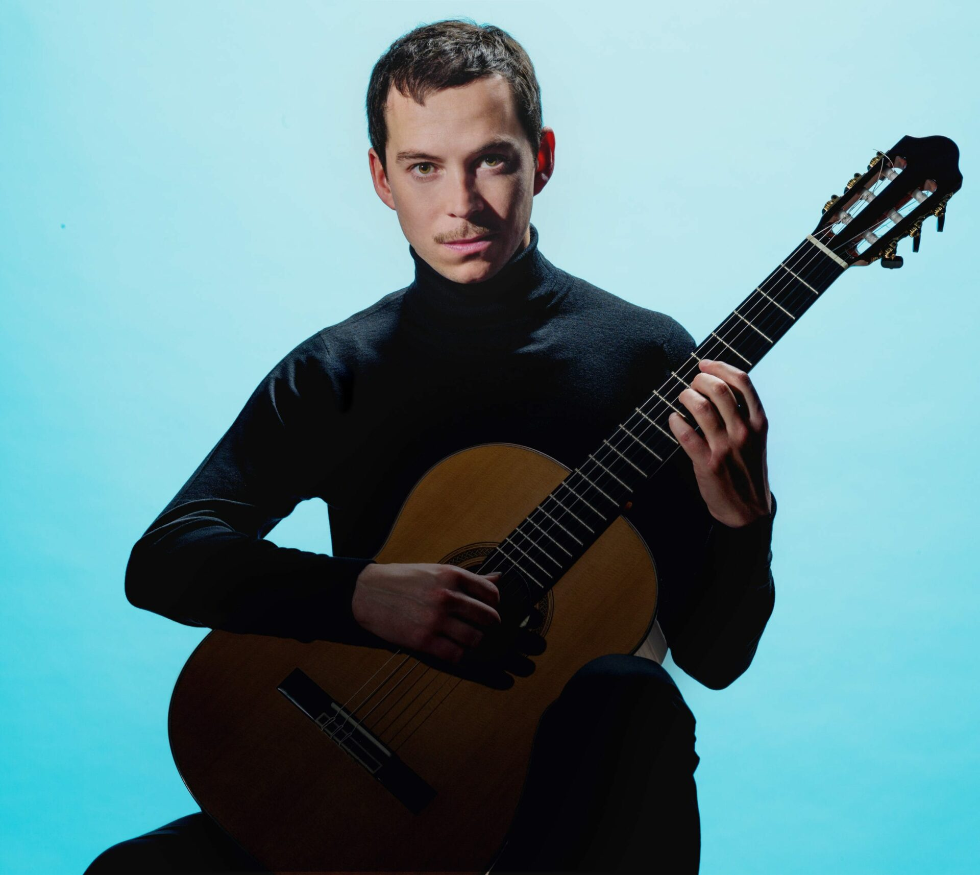 Thibault Cauvin est assis face à nous une guitare à la main et derrière lui se trouve un fond bleu ciel